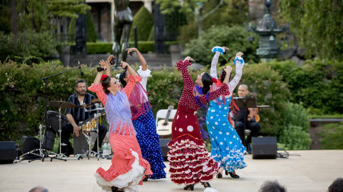 four female flamenco dancers in brightly colored, ruffled dresses perform on an al fresco stage